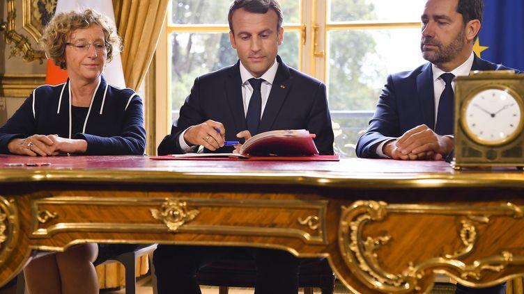 Emmanuel Macron entouré de Muriel Pénicaud et de Christophe Castaner, lors de la signature des ordonnances réformant le Code du travail, le 22 septembre 2017 à l'Elysée. (CHRISTIAN LIEWIG / POOL / REA / ABACA)