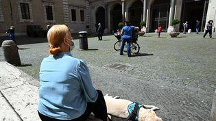 Une femme et son chien dans le quartier deTrastevere à Rome (Italie), le 3 mai 2020. (VINCENZO PINTO / AFP)