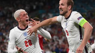 L'attaquantanglais Harry Kane (à droite) et le milieu de terrain Phil Foden célèbrent le penalty converti en prolongation par Kane, le 7 juillet 2021. Un but qui envoie les Three Lions en finale chez eux à Wembley. Le Danemark est éliminé en demi-finale après un parcours mémorable. (LAURENCE GRIFFITHS / AFP)
