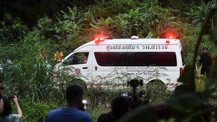 Une ambulance quitte la zone de la grotte de Tham Luang après que des plongeurs aient évacué certains des garçons parmi un groupe de 13 personnes coincées dans une grotte inondée, le 8 juillet 2018. (LILLIAN SUWANRUMPHA / AFP)
