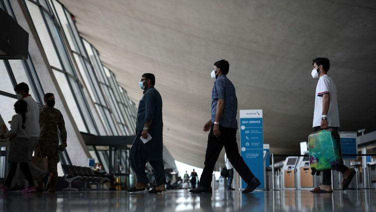 Des réfugiés afghans à l'aéroport de Dulles en Virginie, le 31 août 2021. (ANNA MONEYMAKER / GETTY IMAGES NORTH AMERICA / AFP)