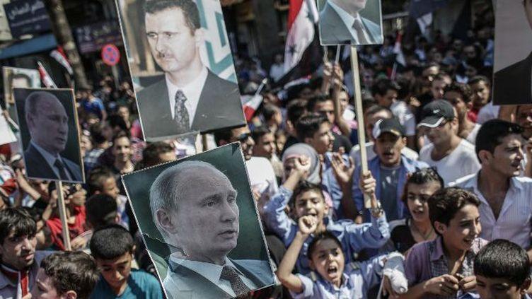 Les effigies des présidents russe, Vladimir Poutine, et syrien, Bachar al-Assad, côte à côte lors d'une manifestation de soutien à Lattaquié, en pays alaouite, le 24 septembre 2013. (Andrey Stenin/Ria Novosti)