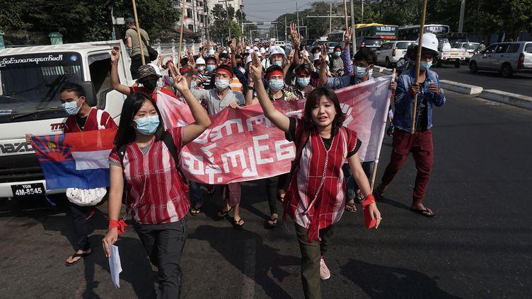 Des manifestants protestent contre le coup d'Etat militaire ayant renverséAung San Suu Kyi, lors d'une manifestation à Rangoun (Birmanie), le 6 février 2021. (STR / AFP)