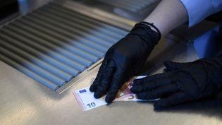 Une caissière à son poste pendant l'épidémie de coronavirus Covid-19. (INA FASSBENDER / AFP)