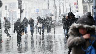 Des passants marchent sous la neige lors d'une vague de froid à Paris, le 5 février 2018. (JULIEN MATTIA / AFP)