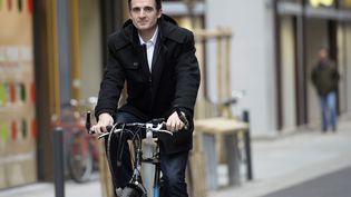 Éric Piolle, le candidat écologiste aux municipales à Grenoble (Isère), le 6 février 2014 à vélo devant sa permanence de campagne. (PHILIPPE DESMAZES / AFP)
