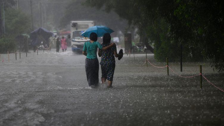 Des femmes marchent sous la pluie, dans le bidonville deShwegyin, dans la région de Bago, le 8 août 2019. (YE AUNG THU / AFP)
