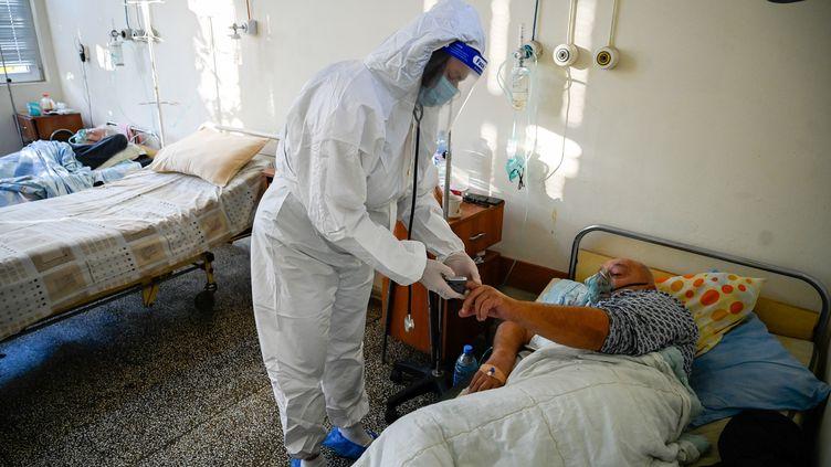 """Un médecin examine un patient à l'unité Covid-19 d'un hôpital de Kjustentendil, l'une des municipalités de la """"zone rouge sombre Covid"""" de Bulgarie, le 19 octobre 2021. (NIKOLAY DOYCHINOV / AFP)"""