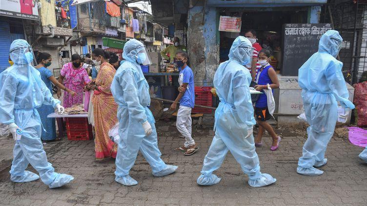 Des soignants et des bénévoles membres d'une organisation nationaliste hindoue participent à un porte-à-porte pour dépister les malades du Covid-19 dans un bidonville de Bombay (Inde), le 17 juin 2020. (INDRANIL MUKHERJEE / AFP)