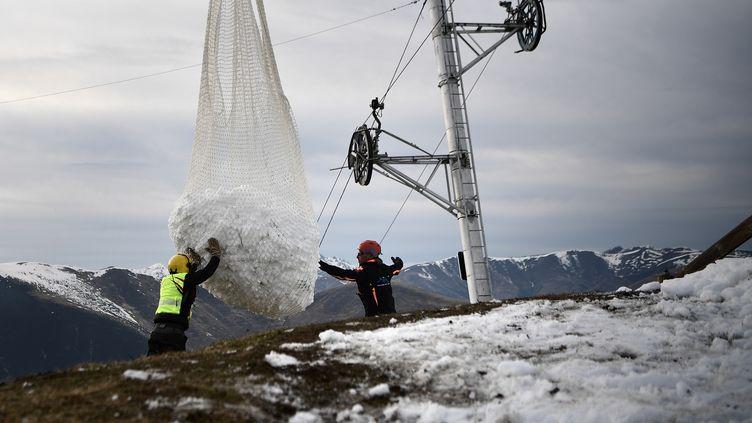 Deux hommes réceptionnent la neige apportée par un hélicoptère pour réenneiger un téléski dans la station pyrénéenne de Luchon-Superbagnères, le 15 février 2020. (ANNE-CHRISTINE POUJOULAT / AFP)