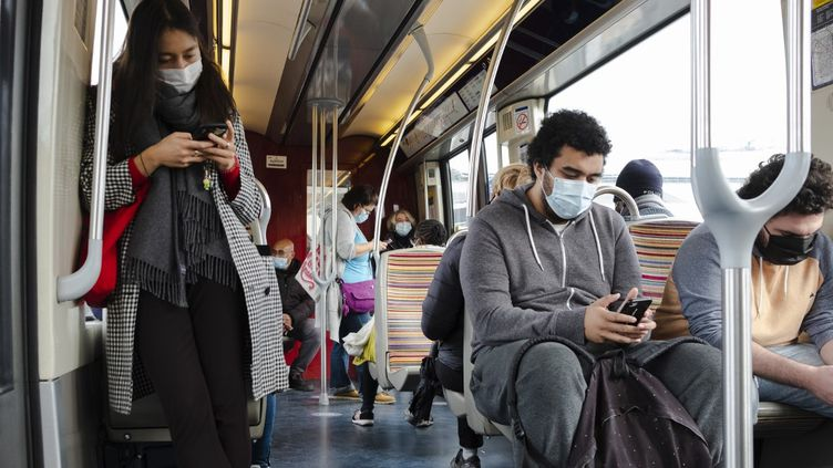 Des personnes regardant leur portable dans le métro à Paris, le 12 octobre 2020. (JEANNE FOURNEAU / HANS LUCAS / AFP)