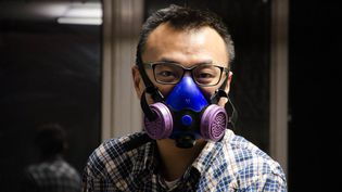 Lorsqu'il va au travail à vélo les jours de pollution, affrontant le trafic pékinois,Chen Mulong porte ce type de masque. (THOMAS BAIETTO / FRANCETV INFO)