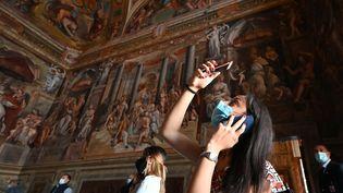 Des touristes visitent l'une des chambres de Raphaël, dans les musées du Vatican, le 1er juin 2020. (ANDREAS SOLARO / AFP)