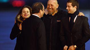 Serge Lazarevic (au centre)accueilli par sa fille, Diane, le président de la République, François Hollande, et Clément Verdon,fils de son compagnon de détention Philippe Verdon, sur la base militaire de Villacoublay, le 10 décembre 2014. (MARTIN BUREAU / AFP)