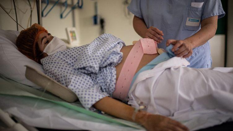 Une sage-femme pratique un examen sur une femme enceinte à la maternité de l'hôpital des Diaconesses, à Paris, le 17 novembre 2020 (MARTIN BUREAU / AFP)