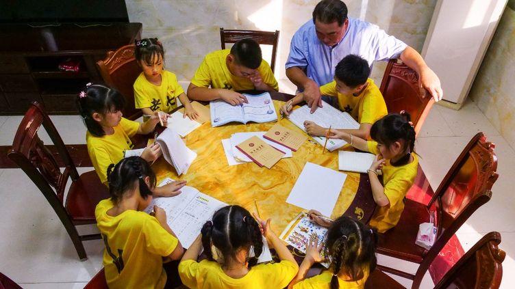 Des enfants font leur devoir à Bangtou en Chine, le 16 août 2021. (ZHOU YI / XINHUA / AFP)