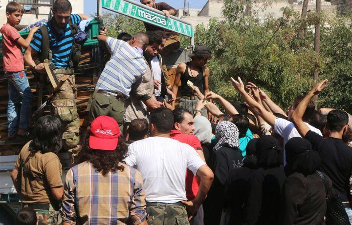 Le 11 août 2016, les habitants d'Alep profitent de l'ouverture du blocus pour acheter des vivres au marché noir. (Abdalrhman Ismail / Reuters)