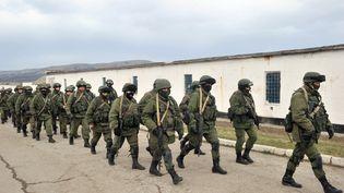 Des hommes armés, sans insigne, bloquent l'accès de la base des gardes-côtes ukrainiens, à Perevalne, près de Simferopol, en Crimée (Ukraine), le 2 mars 2014. (GENYA SAVILOV / AFP)