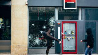 Des manifestants s'attaquent à la vitrine d'unebanque, à Paris, le 5 février 2019. (MARIE MAGNIN / HANS LUCAS / AFP)