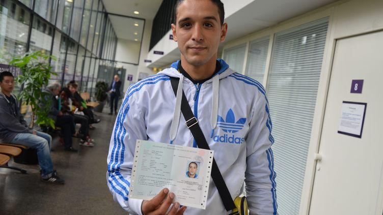 Mohssen Oukassi pose avec son récépissé de demande de carte de séjour, le 17 juin 2014, à la préfecture de Seine-Saint-Denis, à Bobigny. (YANN THOMPSON / FRANCETV INFO)
