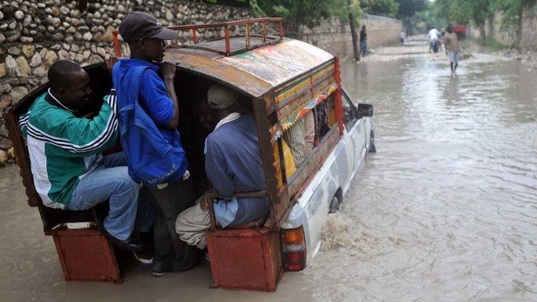 Des habitants de la capitale haïtienne, Port-au-Prince,tentent de traverser une rue inondée, le 25 octobre, après le passage de l'ouragan Sandy. (THONY BELIZAIRE / AFP)