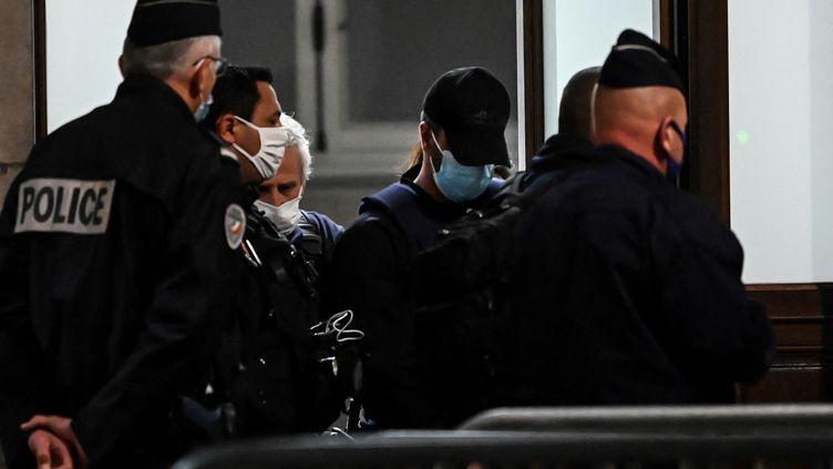 Nordahl Lelandais(au centre) escorté par des policiers, quitte la Cour d'assises à Chambéry, le 11 mai 2021, il vient d'être condamné à20 ans de réclusion criminelle, avec une peine de sûretédes deux tiers, pour le meurtre d'Arthur Noyer. (JEAN-PHILIPPE KSIAZEK / AFP)