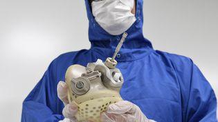 Un employé de Carmat montre un cœur artificiel développé par la société française, 29 août 2018 au siège de Bois-d'Arcy (Yvelines). (BERTRAND GUAY / AFP)