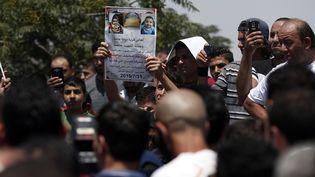 Un homme brandit la photo d'un bébé palestinien tué dans l'incendie de la maison de ses parents,le 31 juillet 2015à Duma en Cisjordanie (Palestine). (THOMAS COEX / AFP)