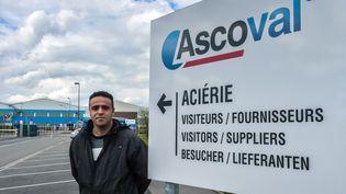 Le syndicaliste CGT Nacim Bardi, 42 ans, pose le 3 avril 2019 à côté du panneau d'entrée de l'aciérie Ascoval à Saint-Saulve (Nord). (PHILIPPE HUGUEN / AFP)