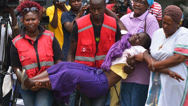 Des membres de la Croix rouge portent, le 3 avril 2015, une personne de la famille d'un étudiant mort dans l'attaque menée à l'université de Garissa (Kenya). (TONY KARUMBA / AFP)