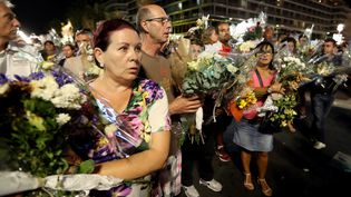 Par brassées, les fleurs déposées depuis l'attentat du 14 juillet sur la chaussée de la promenade des Anglais ont été transportées, lundi 18 juillet, par des centaines d'anonymes dans deux autres lieux de recueillement,à Nice (Alpes-Maritimes). (VALERY HACHE / AFP)