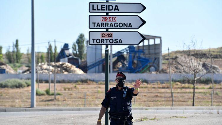 Un policier catalan contrôle les allers et venues des voitures, le 4 juillet 2020, sur une route deLérida(Espagne). (PAU BARRENA / AFP)