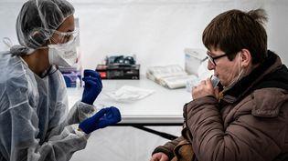 Une femme procède à un test salivaire, le 22 février 2021 à Saint-Etienne (Loire). (JEAN-PHILIPPE KSIAZEK / AFP)