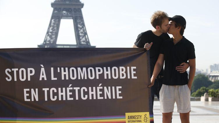 Des militants d'Amnesty international ont déployé une banderole contre les crimes homophobes en Tchétchénie, le 29 mai 2017 à Paris, devant la tour Eiffel. (GEOFFROY VAN DER HASSELT / AFP)