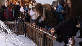Des personnes déposent des bougies dans la station des Deux Alpes (Isère), en hommage aux victimes de l'avalanche, jeudi 14 janvier 2016. (PHILIPPE DESMAZES / AFP)