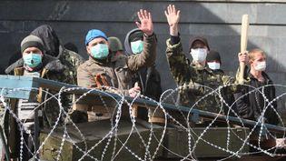 Des activistes pro-russes montent la garde devant une barricade dressée à Donetsk, dans l'est de l'Ukraine, lundi 7 avril 2014. (ALEXANDER KHUDOTEPLY / AFP)