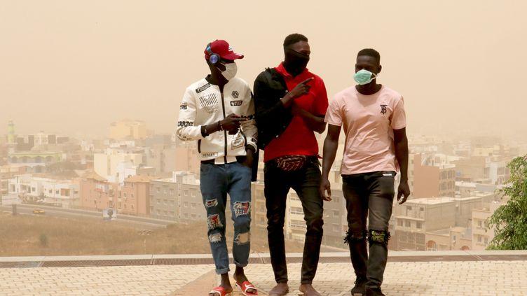 Des habitants de Dakar portant des masques le 25 février 2020 pour se protéger des nuages de poussières sahariens. (ALAATTIN DOGRU / ANADOLU AGENCY)