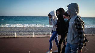 Un groupe de jeunes sur la promenade des Anglais, à Nice (Alpes-Maritimes), le 21 février 2021. (LAURENCE KOURCIA / HANS LUCAS / AFP)