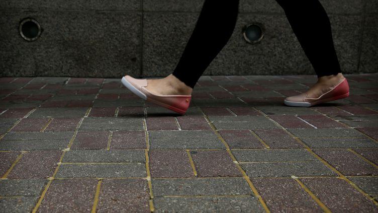 A Hong Kong, les services de la voirie ont déversé de la colle dans les jointures des pavés sur les trottoirs autour du centre de conférences où le numéro trois du pouvoir communiste chinois doit prononcer un discours, indique l'AFP lundi 16 mai 2016. (ISAAC LAWRENCE / AFP)