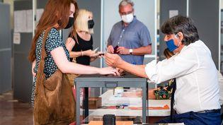 Une femme s'apprête à déposer son bulletin de vote dans l'urne à Perpignan (Pyrénées-Orientales), le 27 juin 2021. (ARNAUD LE VU / HANS LUCAS / AFP)