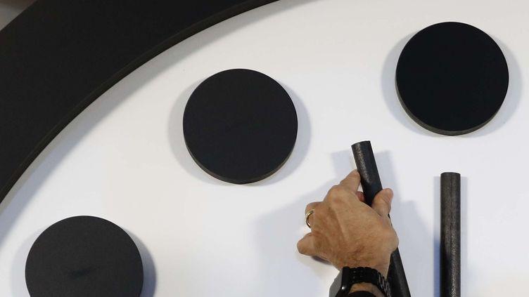 Robert Rosner, alors président du Bulletin of the Atomic Scientists, déplace l'aiguille des minutes de l'horloge de l'apocalypse lors d'une conférence de presse au National Press Club à Washington, le jeudi 25 janvier 2018. (CAROLYN KASTER / AP / SIPA)