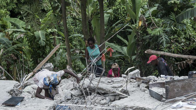 Des habitants au mileu des gravats à Camp-Perrin, en Haïti, le 16 août 2021. (REGINALD LOUISSAINT JR / AFP)