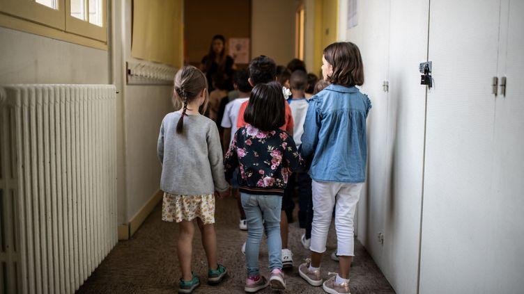 Des élèves rejoignent leur salle de classe, le 2 septembre 2019, à Paris. (MARTIN BUREAU / AFP)