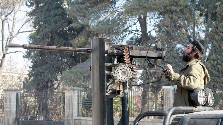 Un combattant rebelle devant le siège de l'Etat islamique en Irak et au Levant à Alep (Syrie), le 8 janvier 2014. (MOHAMMED WESAM / ALEPPO MEDIA CENTRE / AFP)