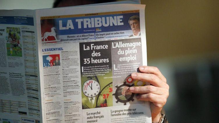 Un homme lit le quotidien économique La Tribune, à Paris, le 5 janvier 2011. (THOMAS COEX / AFP)