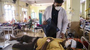 Un médecin aide un patient atteint du Covid-19 à l'hôpital NSSCB de Jabalpur, le 20 mai 2021. (UMA SHANKAR MISHRA / AFP)