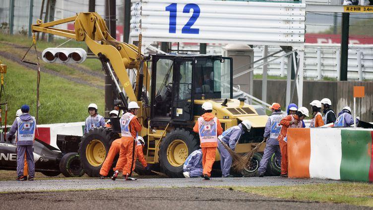 Des secouristes s'affairent autour du véhicule du pilote français Jules Bianchi, lors du Grand prix de Formule 1, le 5 octobre 2014 à Suzuka (Japon). (HOCH ZWEI / AFP)