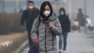 Une femme portant un masque, dans une rue de Pékin (Chine), le 13 février 2020. (KOKI KATAOKA / AFP)