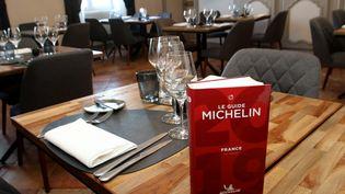 Le guide Michelin sur une table dans un restaurant de Saint-Mont (Gers), le 13 mai 2019. (SEBASTIEN LAPEYRERE / HANS LUCAS / AFP)