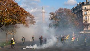Des pompiers professionnels pris dans des nuages de gaz lacrymogène lors de leur manifestation, mardi 15 octobre à Paris. (SEVERINE CARREAU / HANS LUCAS / AFP)